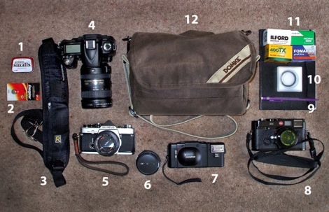 1. Altoids Smalls Tin. 2. Lithium 2L76 Battery. 3. Black Rapid RS-4 Strap. 4. Nikon D90 with 18-200mm Zoom. 5. Olympus OM 2 with 50mm f1.4 Zuiko. 6. 28mm f2.8 Zuiko. 7. Olympus XA with A11 Flash. 8. Leica 'Millennium' M6 TTL Black Paint with 35mm f2 Summicron Asph Black Paint. 9. Notebook & Propelling Pencil. 10. 39mm B+W F-Pro UV MRC Filter. 11. Selection of 35mm Film. 12. Domke F-5XB Rugged Wear Bag.